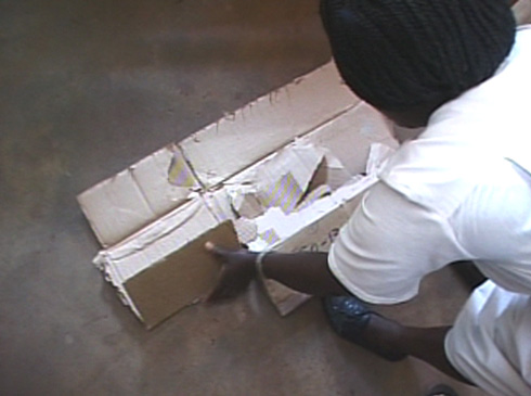 The nurse breaks up a cardboard box to use as a stretcher for the dead body.