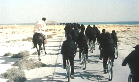 A rider comes looking for his wife amongst the chador clad cyclists.