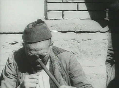 One of the afflicted struggles to light his pipe.